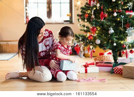 Beautiful young mother with little daughter at Christmas tree at home unpacking presents.