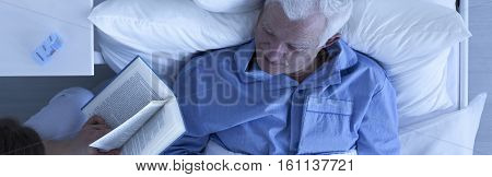 Carer Reading To Senior Sick Man