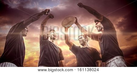 3D Blue and orange sky with clouds against rugby players cheering together with ball