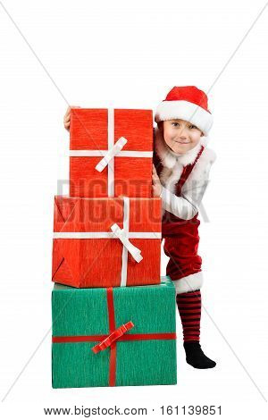 Adorable boy in santa clothes peeks out behind Christmas big gift boxs. Holidays new year x-mas concept. Full length portrait