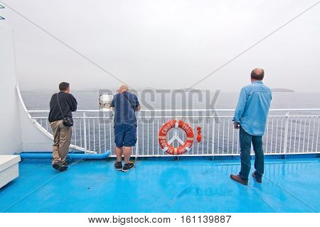 PALMA-IBIZA BALEARIC ISLANDS SPAIN - OCTOBER 25 2016: Three men watch the sea on ferry crossing on an overcast day on October 25 2016 at sea between Palma and Ibiza Balearic islands Spain.