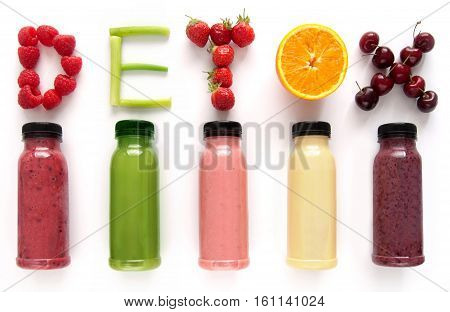 Detox word made with fruits from assorted fruit smoothies over a white background