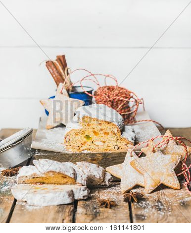 Piece of Traditional German Christmas cake Stollen with festive gingerbread star shaped cookies on rustic wooden table, selective focus, white background, copy space, vertical composition