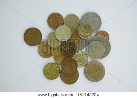 Coins from different europian countries pictured from above on the white background