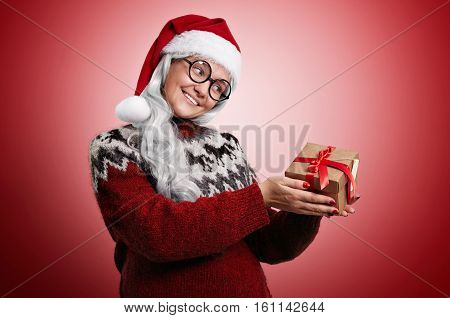 Smiling woman with long white hair wearing Santa hat, glasses and an ugly Christmas sweater looks longingly at a box with a present
