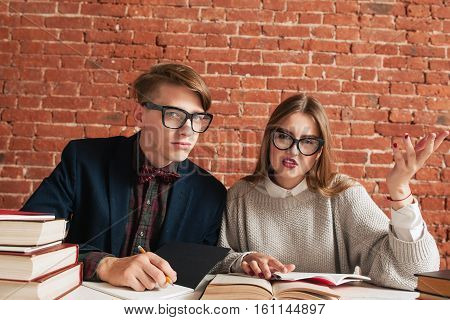 Two students displeased by invasion to their study. Man and woman disturbed while reading material in library. Unpleasure, education, teamwork concept