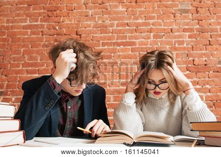 Disheveled man and woman studying at library. Pair of tousled students try to understand hard material, free space on brick wall background. Education, brainstorm, stress, teamwork concept