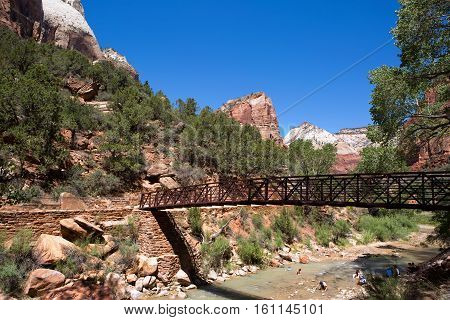 SPRINGDALE UTAH - AUGUST 17 2015: Tourists cool off in the Virgin River as it runs through the valley in Zion National Park Springdale Utah USA on August 17 2015.