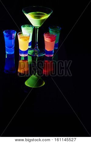 A colored liquid in a cocktail glasses lit by a ultra violet light.