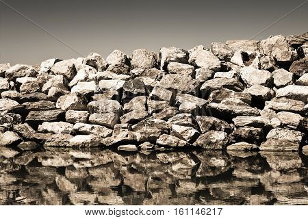 Retaining breakwater wall built with stone boulders