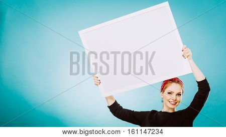 Advertisement concept. Teen smiling girl with blank presentation board. Young female student showing banner sign billboard copy space for text