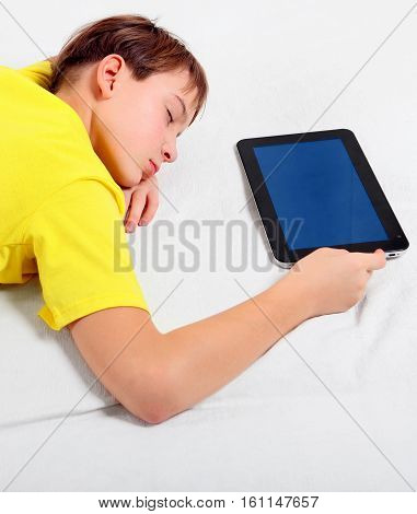 Tired KId sleep with the Tablet Computer on the Bed