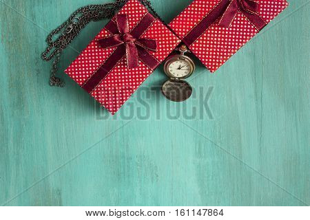 A photo of gift boxes and a vintage chain clock showing the time a little past midnight. A New Year or Christmas greeting card on a teal background with copyspace