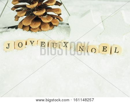 Wooden dices with the words Joyeux Noel in snow French Merry christmas background