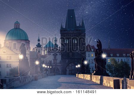 Prague, Czech Republic. Charles Bridge with its statuette at night, Old Town Bridge Tower in the background. Mystical Photo Night Prague.