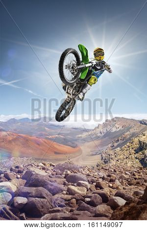 Dirt bike rider is flying high on the top of the vulcan