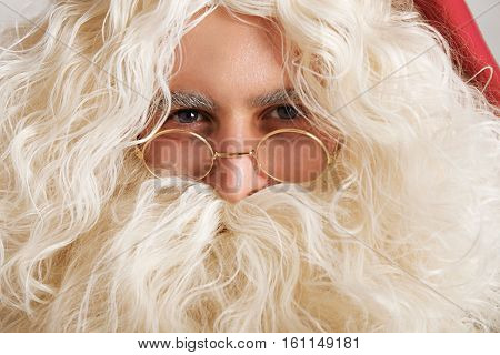 Cute Santa with greyish blue eyes and golden glasses, close up portrait
