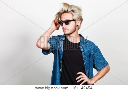 Men fashion modeling concept. Hipster blonde man wearing jeans outfit and sunglasses studio shot