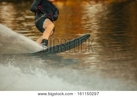 Man riding wakeboard on a lake. Male water skiing and surfing across the lake.