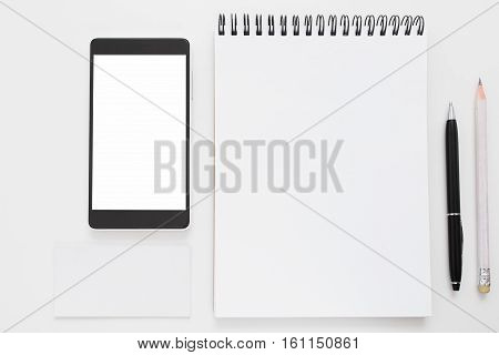 Smartphone and blank notepad flat lay mockup. Top view on white notebook page and empty mobile phone screen with pen and pencil. Memorizing devices development concept