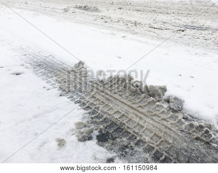 Winter driving car tire tracks in snow with slush during a snow storm with copy space low angle view of dangerous slippery road conditions where winter tires are needed