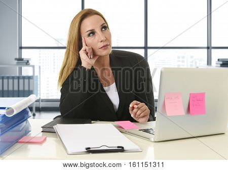 attractive 40s blond businesswoman working at laptop computer sitting on the desk absent minded and thoughtful as if thinking of important business at modern office