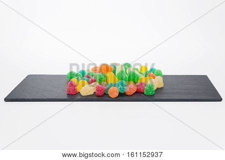 Colorful candy on a dark stone background
