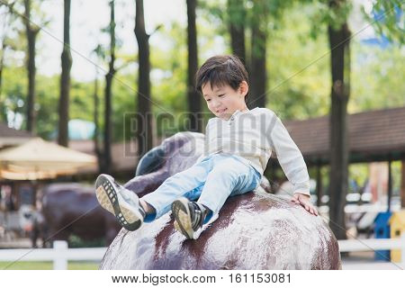 Asian child playing on playground in outdoor park