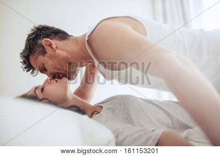 Intimate Young Couple On Bed Enjoying Foreplay