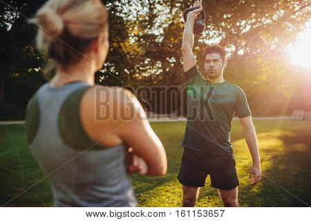 Fit Man Exercising With Female Trainer In Park