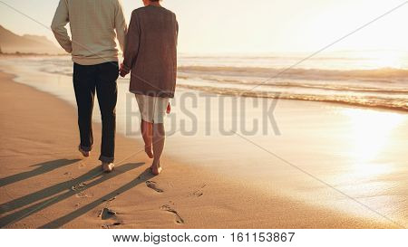 Senior Couple Holding Hands Walking On The Beach
