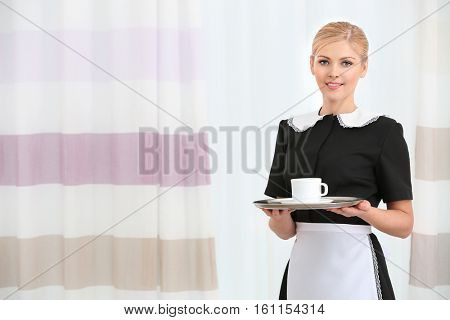 Hotel service concept. Chambermaid holding tray with cup of coffee and standing near window