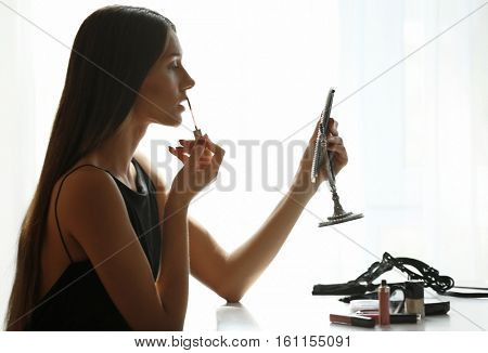 Young beautiful woman doing her make up