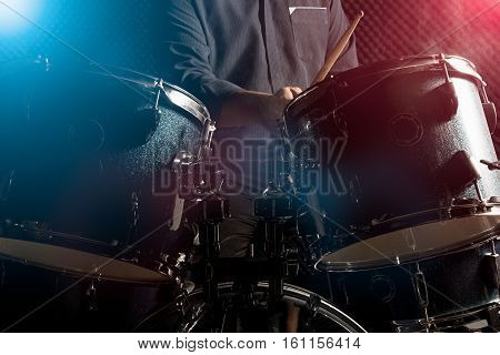 The man is playing drumset in low light background.