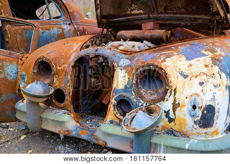 Old classic cars with rust taken in a rural countryside junkyard