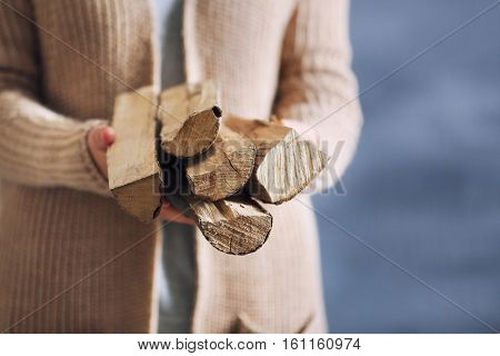 Woman holding pile of firewood, close up view