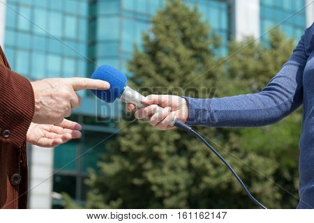 Female reporter holding microphone interviewing business person or politician