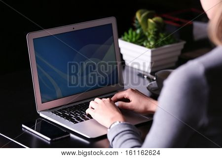 Woman working with laptop in cafe