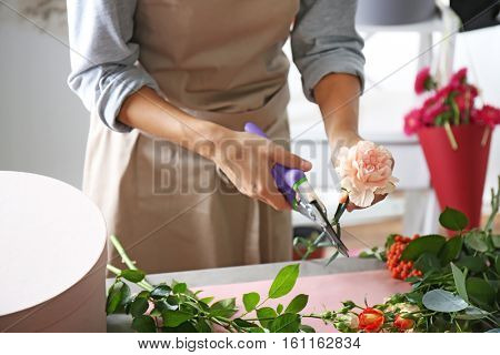 Female florist hands making composition with flowers closeup