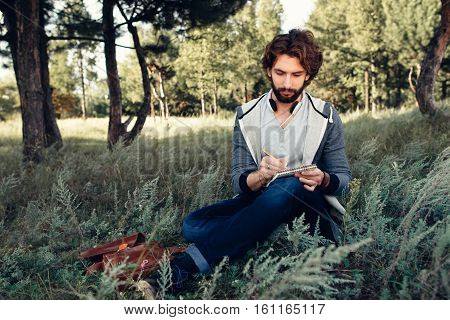 Young poet writing in his sketchbook in forest. Attractive man have rest while walking at nature, copy space for text. Idea, inspiration, afflatus concept