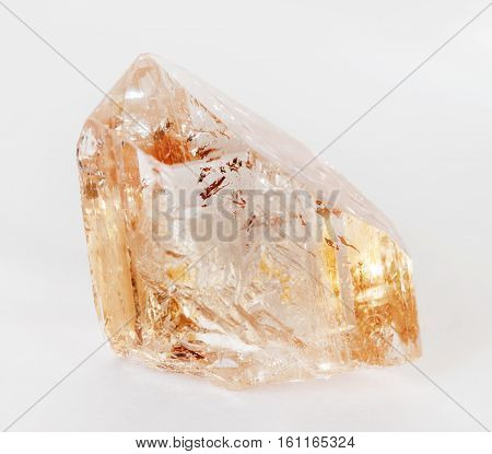 Natural crystal of clear precious wine topaz on a white background