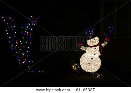 Happy snowman decoration lit up at night