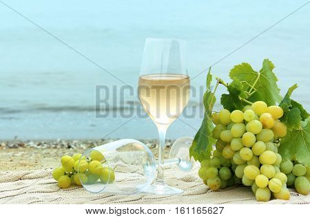 Glasses of wine and fresh grapes on beach