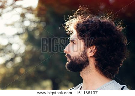 Profile portrait of bearded man in park, free space. side view on serious hipster face, blurred tree background. Hairstyle, barbershop, fashion, modern lifestyle concept