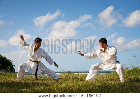 Combat and extreme sports. Hispanic men exercising in karate and traditional martial arts. Simulation of fight on the beach near the sea