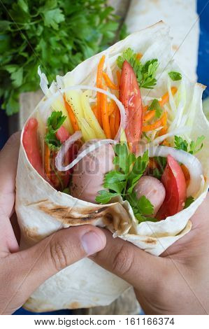 Hot dog in hand on weight - sandwich with sausage in pita, Korean carrots, tomatoes, onions, parsley and pepper