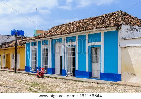 TRINIDAD, CUBA - MARCH 23, 2016: Red motorbike in front of a colonial house on the cobblestone streets in the UNESCO World Heritage old town of Trinidad Cuba