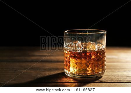 Glass of whisky on wooden table closeup