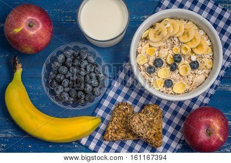 Useful and very tasty breakfast, oatmeal flakes, blueberries, bananas, milk, peaches and kozinaki, Georgian sweets