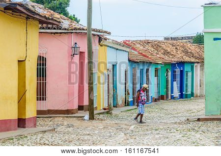 TRINIDAD, CUBA - MARCH 23, 2016: Local man crossing the cobblestone street in the UNESCO World Heritage old town of Trinidad Cuba